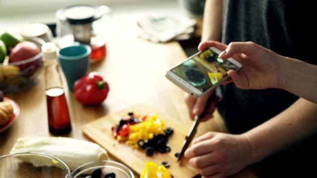 close-up of man hands cutting vegetables for salad and his girlfriend taking photos on smartphone camera for social media in the kitchen at home - cooking filmów i materiałów b-roll