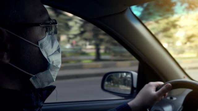 Closeup of man hands on steering wheel driving car during pandemic of corona virus covid-19