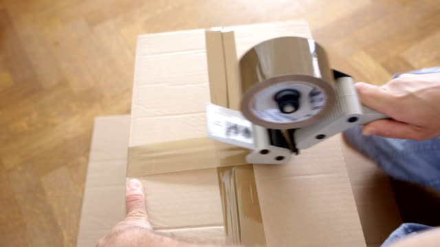 Close-up of man makes cartons for his move - House Moving Concept video