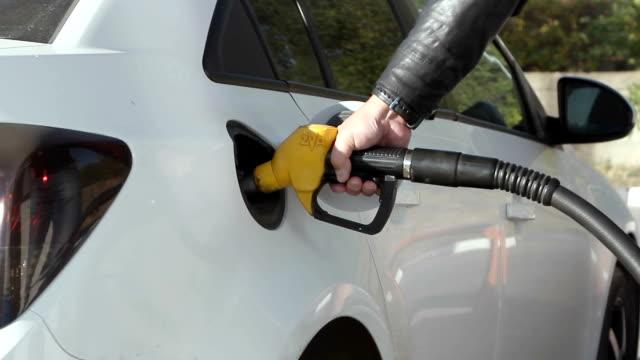 closeup of man pumping gasoline fuel in car at gas station. - заправляться стоковые видео и кадры b-roll