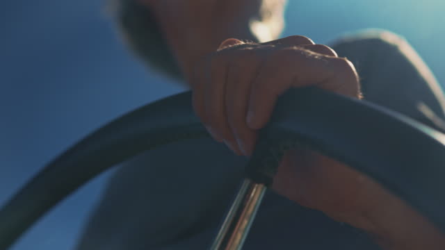 Close-up of man steering in yacht on sunny day