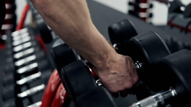 close-up of man takes dumbbell in gym. closeup of dumbbells row - sala gimnastyczna miejsce rekreacji filmów i materiałów b-roll