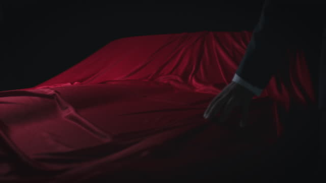 close-up of man touching red satin covered on car - coprire video stock e b–roll