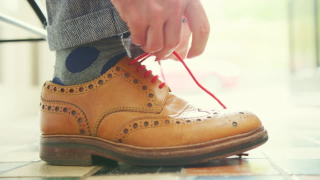 Closeup Of Man Tying The Lace On Tan Brogues