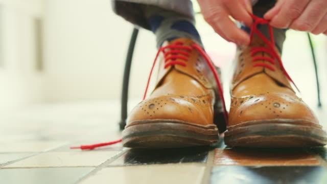 vídeos de stock e filmes b-roll de closeup of man tying the laces on tan brogues - membro
