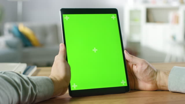 Close-up of Man Using Green Mock-up Screen Digital Tablet Computer in Portrait Mode while Sitting at His Desk. In the Background Cozy Living Room.