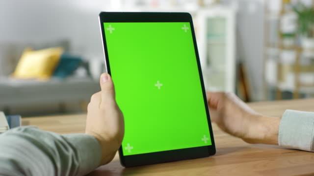 nahaufnahme der mann mittels gesten auf dem grün mock-up bildschirm digital tablet pc im hochformat und sitzt an seinem schreibtisch. im gemütlichen wohnzimmer hintergrund. - schriftrolle stock-videos und b-roll-filmmaterial