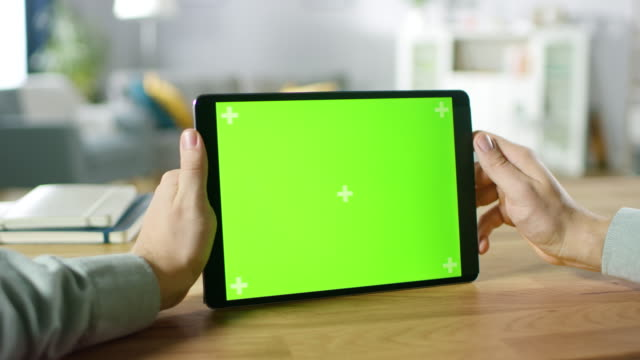 Close-up of Man Using Hand Gestures on Green Mock-up Screen Digital Tablet Computer in Landscape Mode while Sitting at His Desk. In the Background Cozy Living Room.