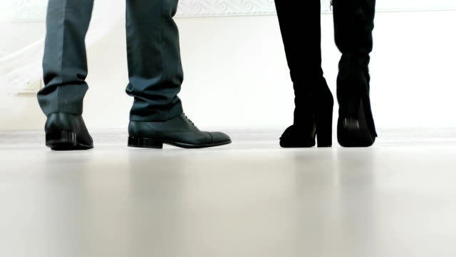 closeup of mans and womans legs walking together wearing leather shoes and boots video