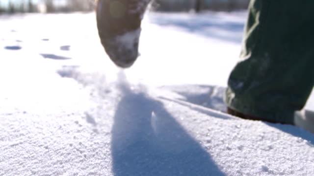 vidéos et rushes de gros plan des pieds de l'homme marcher sur la montagne dans la neige. tournage de ralenti - bottes