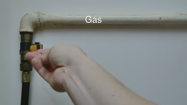 close-up of mans hand close and open gas pipe valve