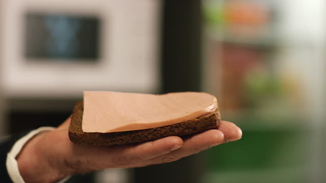 close-up of man's hand holding a piece of borodino rye bread with slice of doctor's sausage falling on it. stock footage. delicious sausage sandwich - mortadella video stock e b–roll