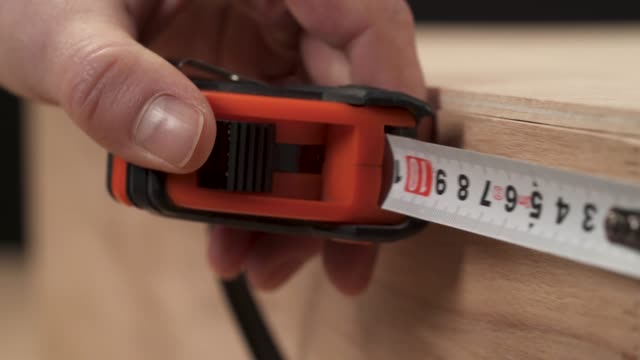 a close-up of man's hand measuring with a flexible ruler the length of wooden workpiece - длина стоковые видео и кадры b-roll