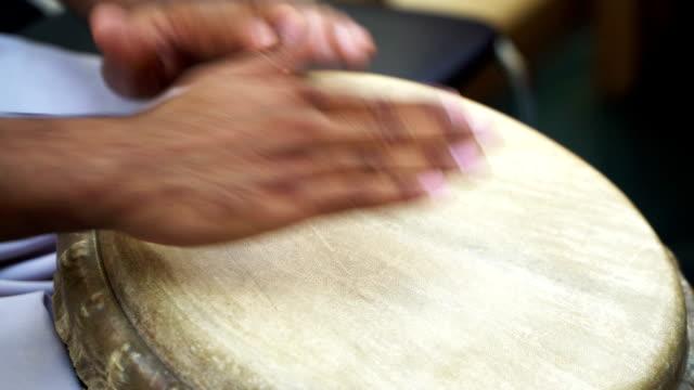 närbild av mannens händer trumma ut ett beat å en hud-täckt bongo drum 1 - latino music bildbanksvideor och videomaterial från bakom kulisserna