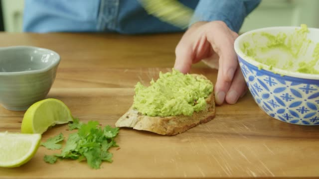 close-up of man's hands making avocado on toast - avocado video stock e b–roll