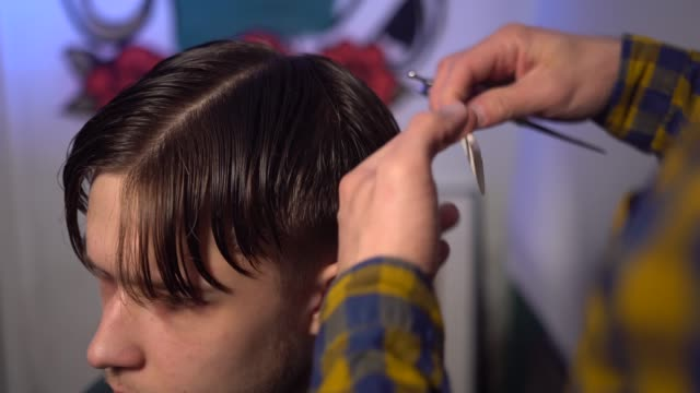 Close-up of master cut hair of young man using scissors with comb video