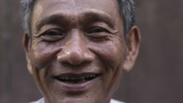 Close-up of mature asian man smiling and looking at camera video