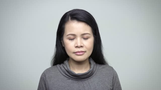 Close-up of mature businesswoman with eyes closed Close-up of mature businesswoman with eyes closed. Female professional is having long black hair. She is wearing smart casuals against white background. eyes closed videos stock videos & royalty-free footage