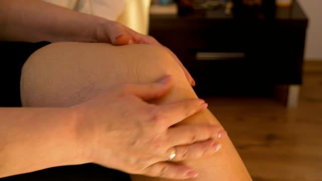 vídeos de stock, filmes e b-roll de closeup de madura mulher casada cuidadosamente massageando seu joelho reumático em casa na cama - articulação humana