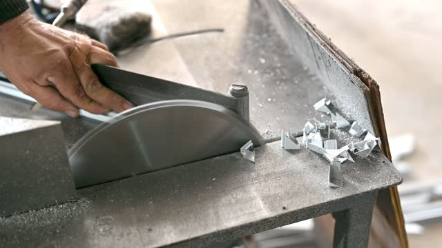 Close-up of mechanical engineer cutting steel with with electric saw