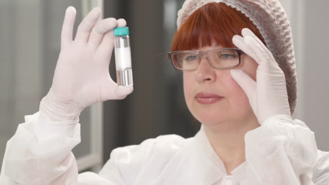 A close-up of medical laboratory technician holding and examining a tube with human biological sample. Scientific research concept.