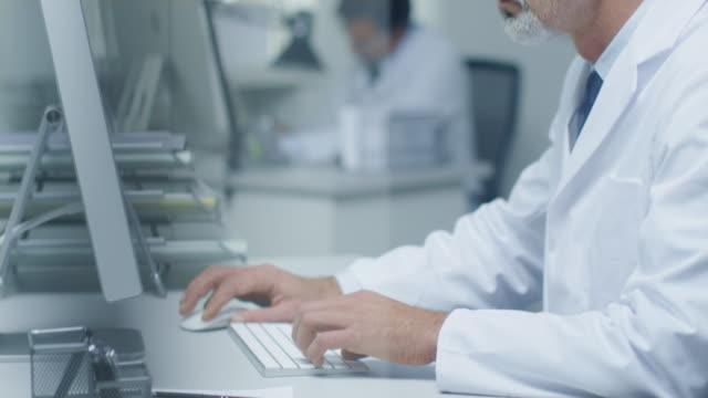 närbild av medicinsk practitioner skriva på ett tangent bord som arbetar på sin station ära dator. i bakgrunden hans assistent arbetar. - looking inside inside cabinet bildbanksvideor och videomaterial från bakom kulisserna