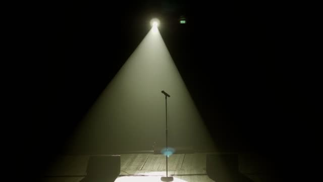Close-up of microphone on stage with white lighting and smoke.