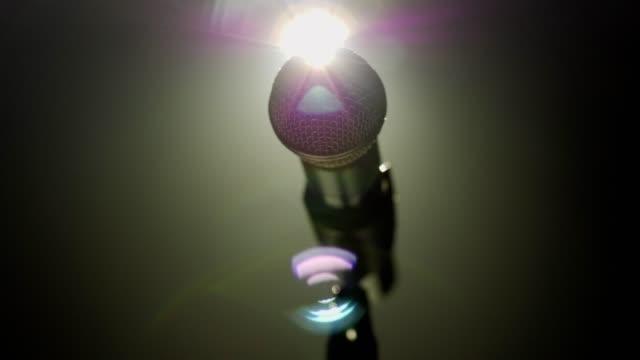 close-up of microphone on stage with white lighting and smoke. - sztuka kultura i rozrywka filmów i materiałów b-roll