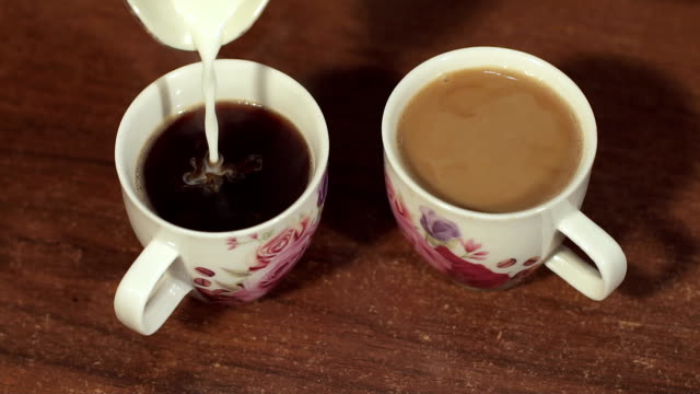 Close-up of milk pouring into the two coffee Cup. video