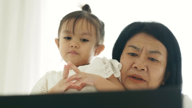 Close-up of Modern life of Thai mother and her daughter are watching cartoon on computer laptop at their bedroom for leisure activity -relative of mother and her baby with Mother's day concept video