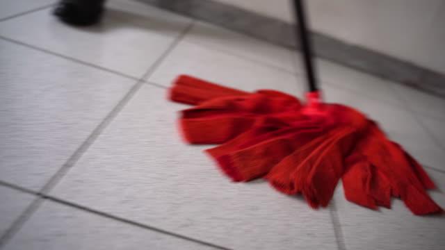 nahaufnahme von mopping boden, filmischen rahmen von beweglichen mop auf nassen boden. magd waschen schmutzigen boden, sauberkeit und hygiene zu hause oder imbüroraum. beputzboden und sanierungskonzept - eimer stock-videos und b-roll-filmmaterial
