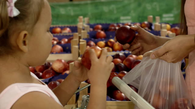 close-up of mother and little daughter choosing fruits in supermarket. - pesche bambino video stock e b–roll