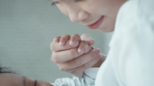 Close-up of mother holding baby's hand,Slow motion