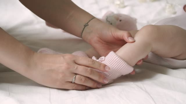 Close-up of mother's hands dress booties to the baby Close-up of mother's hands dress booties to the baby baby booties stock videos & royalty-free footage