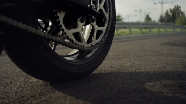 Closeup of motorcycle tire spinning on the road Spinning motorcycle tire on the road with green grass and trees on the roadside at lovely sunny day. 90fps motorcycle stock videos & royalty-free footage