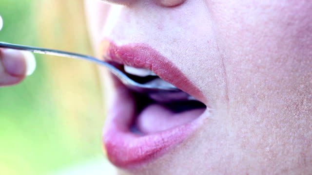 Close-up of mouth an attractive young woman eating yogurt video