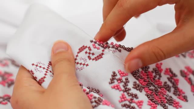 primo primo di ago e filo, ricami con perline. abito da sposa da cucito fatto a mano. - braccio umano video stock e b–roll