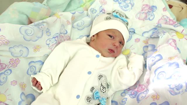 Nahaufnahme des Neugeborenen in weißen Hut liegt auf Bett. – Video