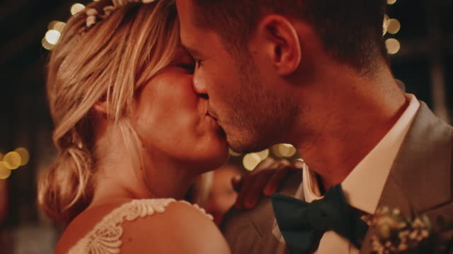 Close-up of newlywed couple kissing while dancing Close-up of young married couple kissing while dancing in party. Happy bride and bridegroom enjoying on illuminated dance floor. They are celebrating at wedding reception during night. newlywed stock videos & royalty-free footage