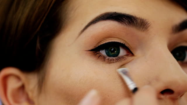 Close-up of of a beautiful young woman with esthetician making makeup applying concealer. Close-up of of a beautiful young woman with esthetician making makeup applying concealer. foundation make up stock videos & royalty-free footage