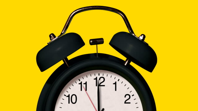 Closeup of old fashioned Black alarm clock rings on yellow Background