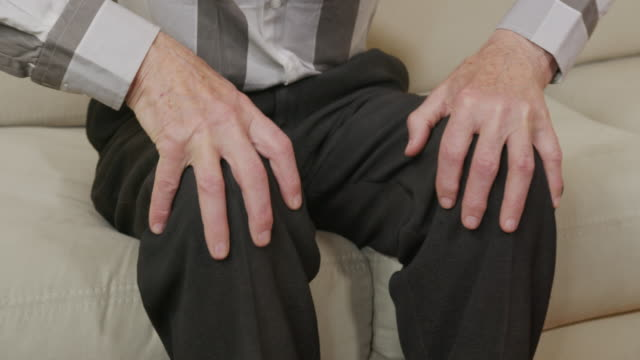 Closeup of old man hands lie on his lap.