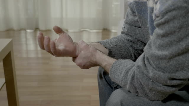 Closeup of old man with arthritis touching his painful wrist having rheumatism sitting on the couch at home video