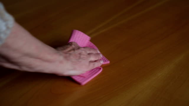closeup of old woman's hand cleaning a table video