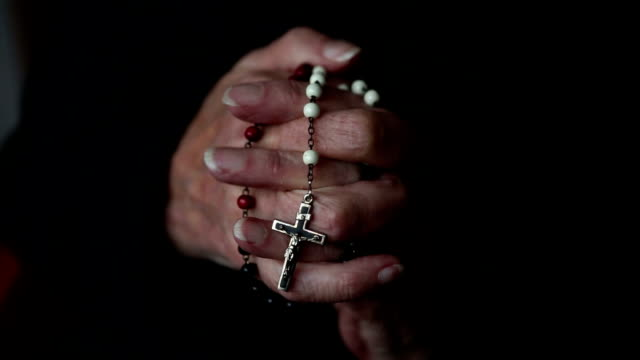 closeup of old woman's hands praying and holding a rosary video