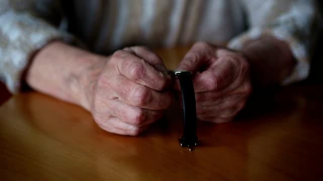 närbild av gamla kvinnans händer ställa in tiden på hennes klocka - armbandsur bildbanksvideor och videomaterial från bakom kulisserna