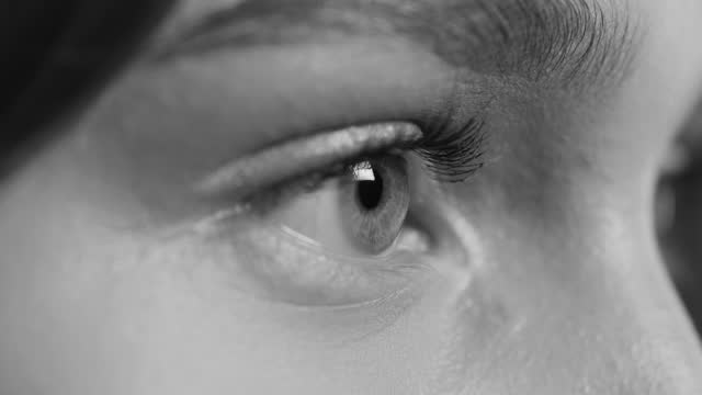 Close-up of one eye of a girl, side view. Black and white video. video