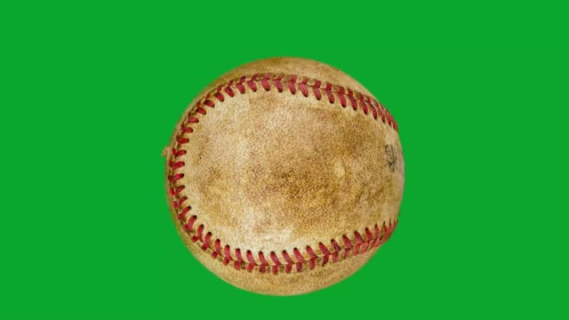 close-up of one old baseball rotating on green screen background