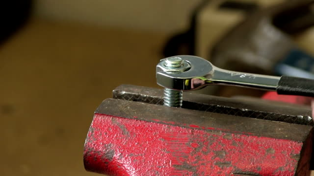 closeup of open wrench tightening nut with sound video