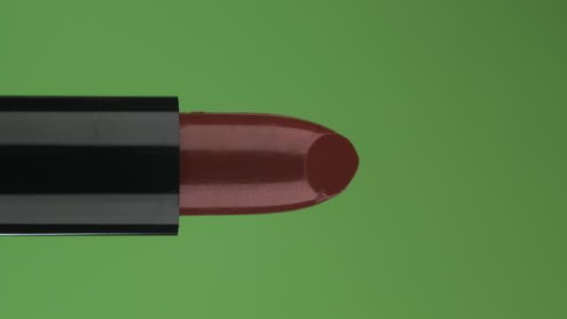 Plan rapproché du rouge à lèvres d'ouverture. Rouge à lèvres rouge d'ouverture isolé sur l'écran vert. - Vidéo